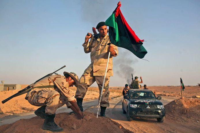 Archiefbeeld. Rebellen planten een vlag nadat ze de stad Bani Walid hebben veroverd op loyalisten van Khadafi. (18/09/2011)
