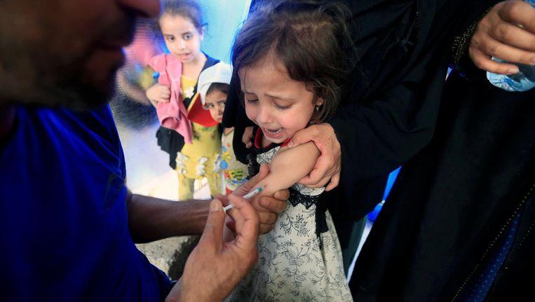 Een Iraaks meisje gevlucht van terreurgroep Islamitische Staat krijgt een vaccinatie in het bevrijde Mosoel.