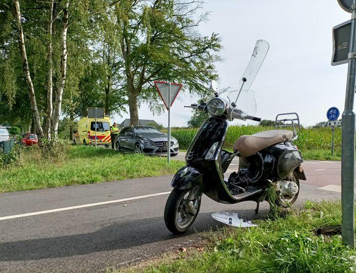 De scooter is door het ongeval flink beschadigd. Op de achtergrond de auto waarmee de scooterrijdster in botsing kwam.