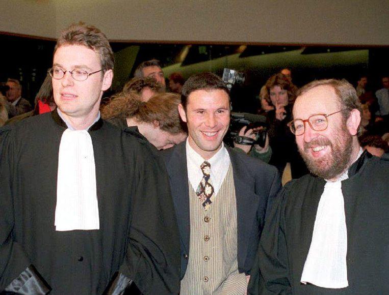 Jean-Marc Bosman, tussen zijn advocaten Luc Misson (R) en Jean-Louis Dupont (L). Beeld BELGA/AFP