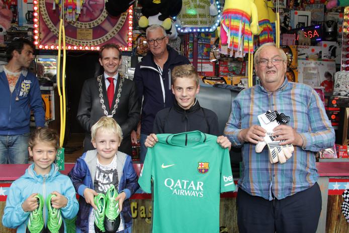 Luuk Leenders toont trots het zojuist gewonnen keepersshirt van Jasper Cillessen. Op de achtergrond, met ketting, burgemeester Mark Slinkman.