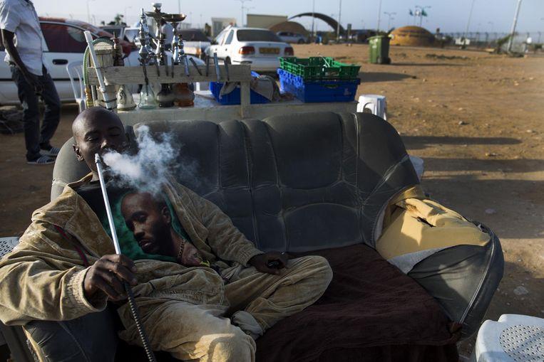 Een vluchteling rookt waterpijp voor het detentiecentrum in de Negev woestijn. Beeld ap