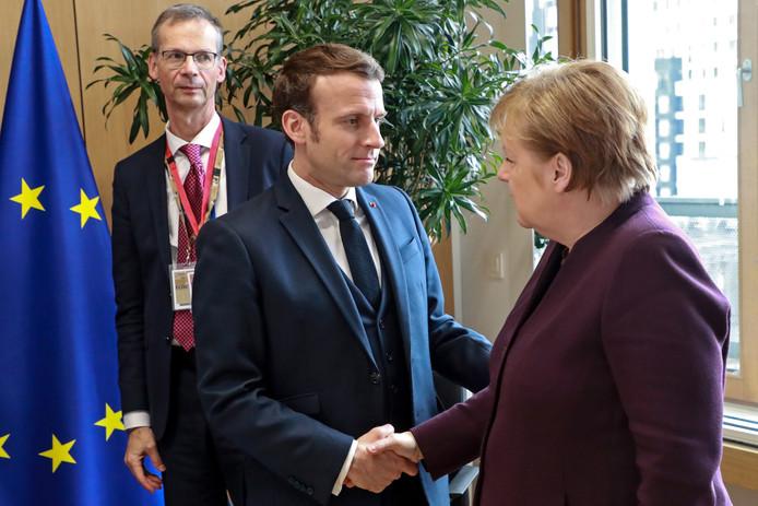 De Duitse bondskanselier Angela Merkel (rechts) en de Franse president Emmanuel Macron begroeten elkaar tijdens de EU-begrotingstop in Brussel.