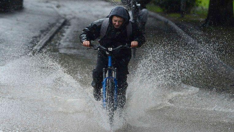 Een jongen in Morpeth probeert dinsdag overeind te blijven op de fiets tijdens een hevige regenbui. Beeld REUTERS