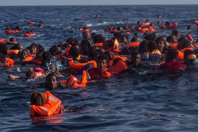 Vluchtelingen vechten voor hun leven op de Middellandse Zee nadat hun boot kapseisde. Foto genomen in maart dit jaar, voor de kust van het Italiaanse eiland Lampedusa. Beeld getty