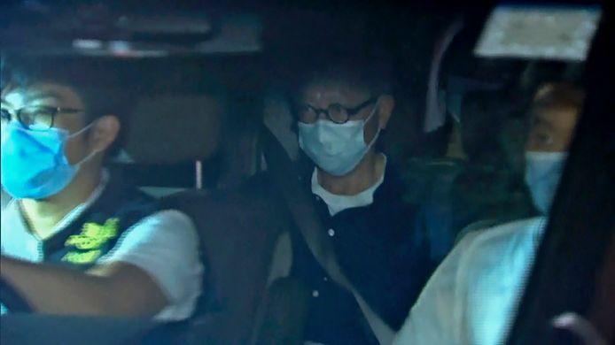 Hoofdcolumnist Fung Wai-kong in politiewagen na arrestatie in Hongkong.