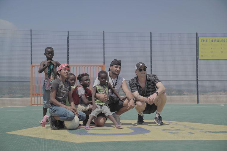 De populaire Nederlandse Youtuber Kalvijn, ambassadeur van de Cruyff Foundation, met kinderen uit het vluchtelingenkamp op het Cruyff Court op Lesbos.  Beeld rv