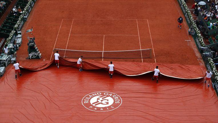 Een zeil beschermt het gravel tegen de regen. 'Het is niet uit te leggen dat ik sterren als Djokovic en Serena Williams naar hun hotels moet sturen', zegt de toernooidirecteur. Beeld EPA