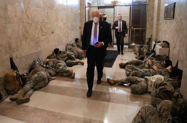 Leider van de Democrate, Steny Hoyer, loopt langs leden van de 'National Guard'. Zij waren in het gebouw van het parlement om nieuwe bestormingen te voorkomen. Beeld AFP