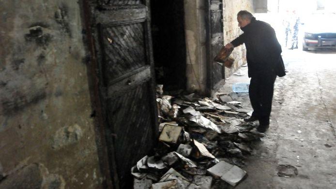 Een man overziet de stapel met verbrande boeken in Tripoli.