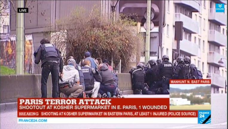 De politie in de buurt van de winkel waar mensen worden gegijzeld. Beeld Screenshot 24France