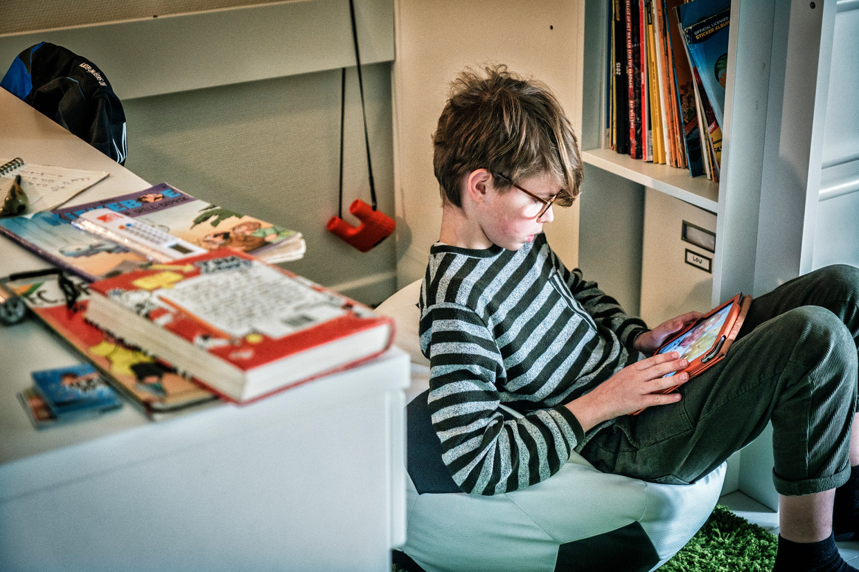 Lou (10) en zijn iPad: 'Als ik zelf iets post of een spelletje download, dan toon ik mama en papa altijd wel eerst waarover het gaat.' Beeld Tim Dirven