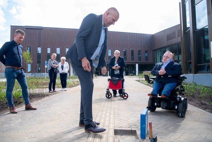 De laatste tegel ligt klaar om de nieuwe stoep bij het gemeentehuis van Dalfsen helemaal af te maken.