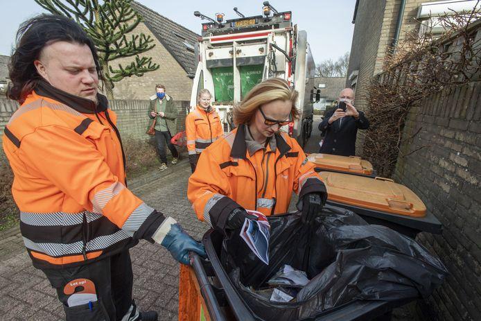 Wroeten in een plasticafval container: voor Nick Vos (links) en Nicole Postma is het een kwestie van goed zoeken. Zo zit in deze container opvallend veel oud papier.