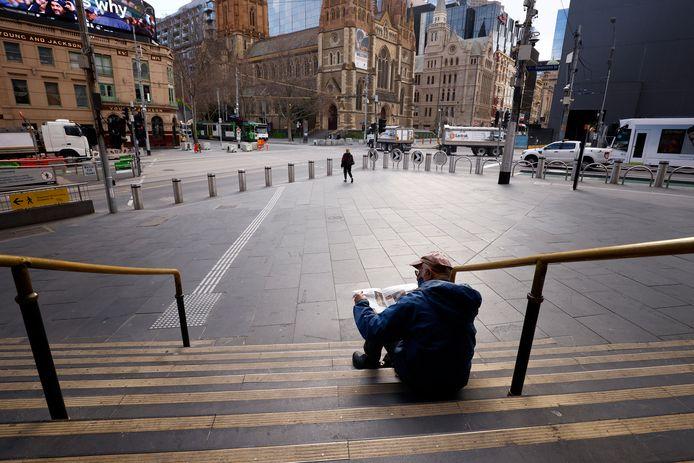 Een man leest de krant op de trappen van Flinders Street Station in Melbourne.