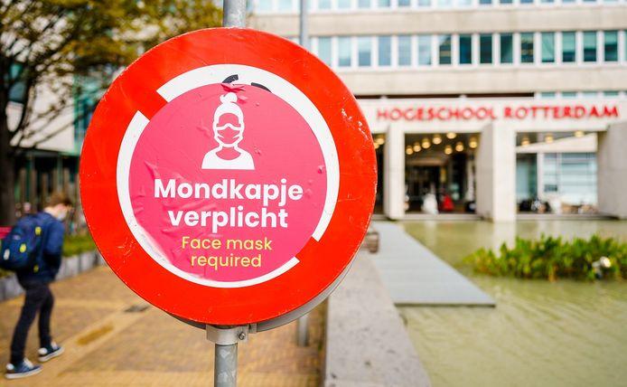 Een bord wijst studenten van de Hogeschool Rotterdam op de mondkapjesplicht.