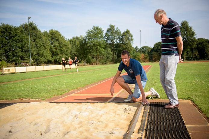 Voorzitter Ben Lathouwers (knielend) van AVR'69 is blij dat enkele afgekeurde onderdelen van de atletiekbaan nu gerenoveerd worden.
