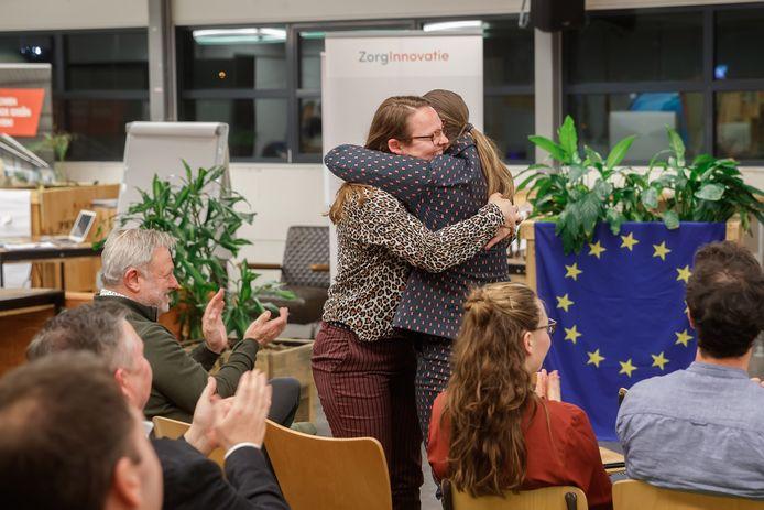 Edith Raaijmakers (l) en Maartje Huggers, beiden moeder van een kind met beperkingen, vallen elkaar in de armen als ze horen dat ze de Zorginnovatieprijs Midden- en West-Brabant en Zeeland hebben gewonnen.