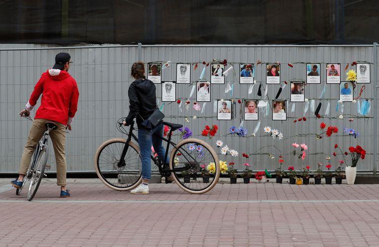 Voorbijgangers kijken naar een herdenkingsmuur van aan covid-19 overleden zorgmedewerkers in Sint Petersburg.   Beeld EPA