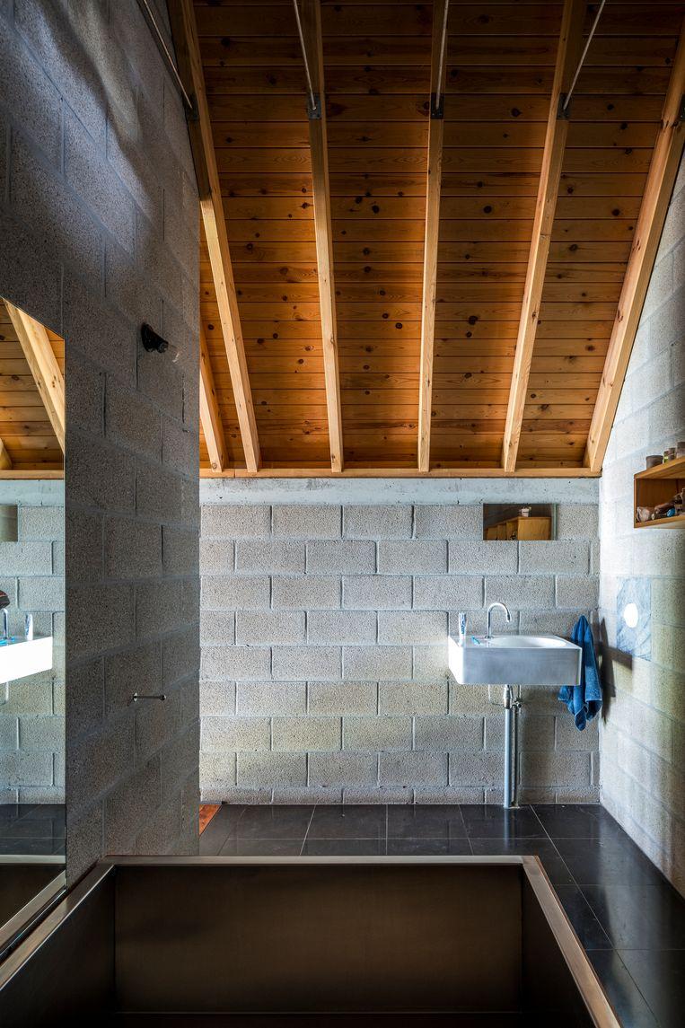 De badkamer met inox bad die paalt aan Delbroeks slaapkamer op de tweede verdieping.  Beeld Luc Roymans