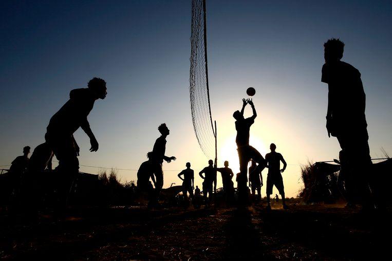 Ethiopiërs volleyballen in het vluchtelingenkamp Um Raquba in Soedan. Deze maand braken zware gevechten uit in de Ethiopische provincie Tigray, waardoor een vluchtelingenstroom op gang kwam. Inmiddels verblijven zo'n 36.000 Ethiopiërs in het buurland.  Beeld AFP