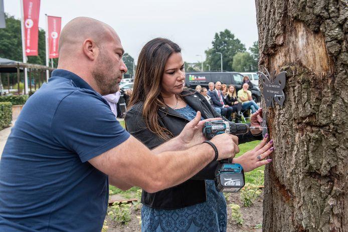 Daniël van Berlo en Nancy Pudelko hangen vlinders op ter nagedachtenis aan hun overleden vaders, die beiden door geweld omkwamen.