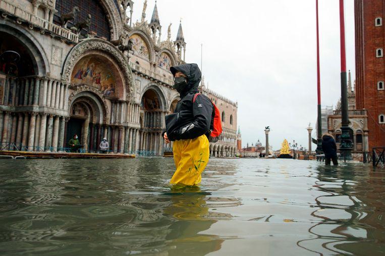 Voetgangers in Venetië waden dinsdag over het San Marcoplein dat ondanks de nieuwe dam weer onder water staat. Beeld AP