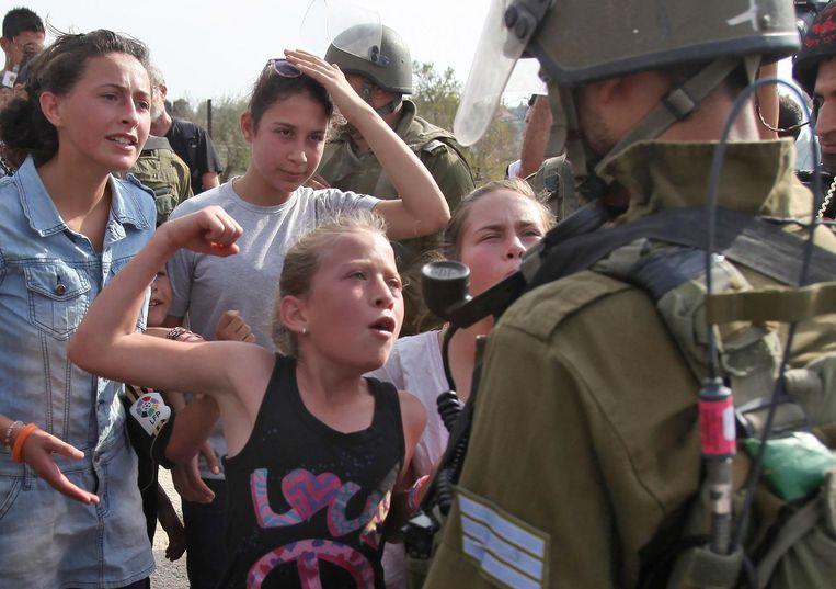 Ahed Tamimi wisselt wat woorden met een Israëlische soldaat, in 2012. Beeld afp