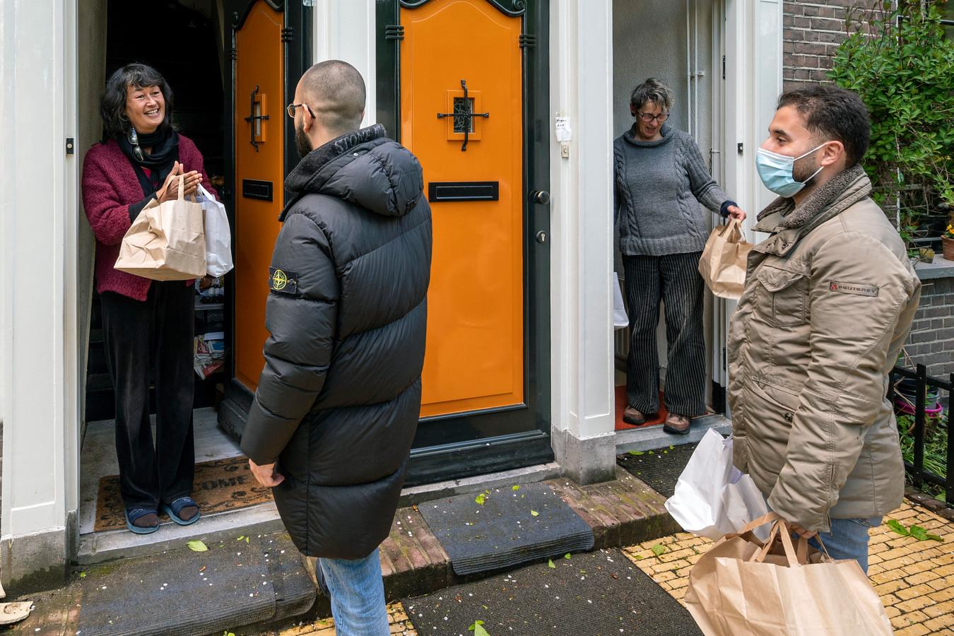 """Moslims van moskee Al Fath delen eten uit aan bewoners van de Van Oldenbarneveldtstraat. ,,Linzensoep, rijst, gemarineerde kip, salade en dadels."""""""