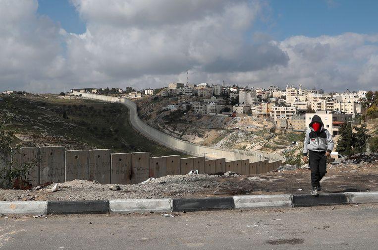 Een jonge Palestijn wandelt langs de omstreden Israëlische muur, in het bezette dorp Abu Dis, dat Trump voorstelt als de hoofdstad van de nieuwe Palestijnse staat. Beeld AFP