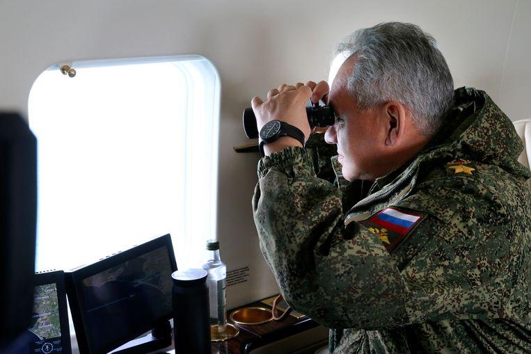De Russische minister van defensie Sergej Sjogoe kijkt vanuit een militaire helikopter toe hoe het Russische leger oefeningen houdt op de Krim. Niet veel later kondigde hij de aftocht van de troepen aan. Beeld AP