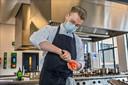 Daan Bokken in actie tijdens de praktijkles: 'Ik vind het geweldig om mensen blij te maken met eten'.