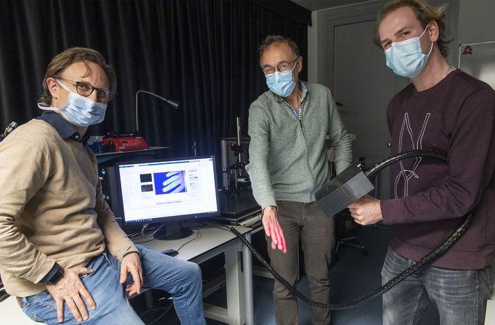 ZGT-arts Hinne Rakhorst (links), professor Wiendelt Steenbergen (midden) en technicus Tom Knop werken aan een scanner die weefsel detecteert. Op de foto ontbreekt teamlid Ata Chizari.