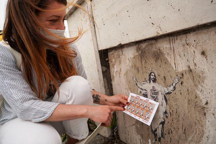 De straatartieste Alessia Babrow toont haar afbeelding van Jezus en de postzegels van het Vaticaan.
