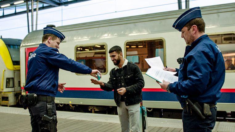 Een man krijgt ontsmettingsgel op zijn handen van een politieagent in het station.  Beeld VTM