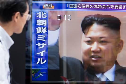 Een man stapt voorbij een scherm met de Noord-Koreaanse leider Kim Jong-un in Tokio.