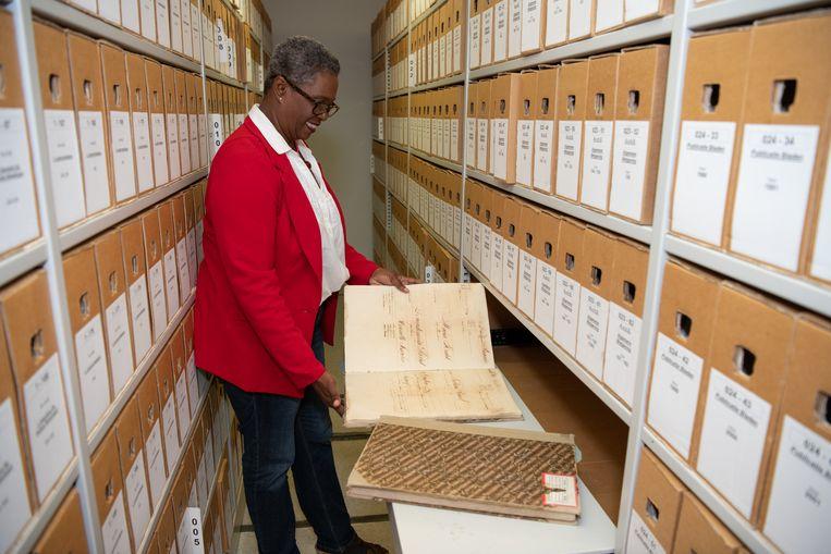 Archivaris Modianne Cathalina met de slavenregisters in het Nationaal Archief van Curaçao Beeld Berber van Beek
