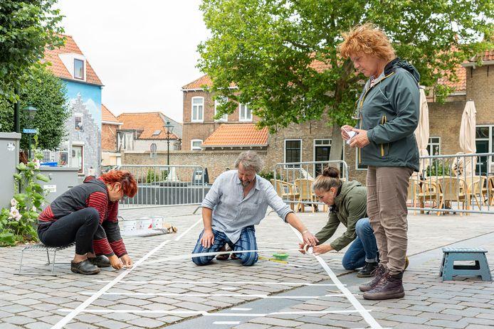 Op Plein Montmaertre in Zierikzee wordt het Silly Walk zebrapad afgeplakt. Initiatiefnemer Christel Brunger, Patrick Veenendaal, kunstenares Inge de Groot en Leonie van der Pluijm (vlnr) zijn er druk mee.