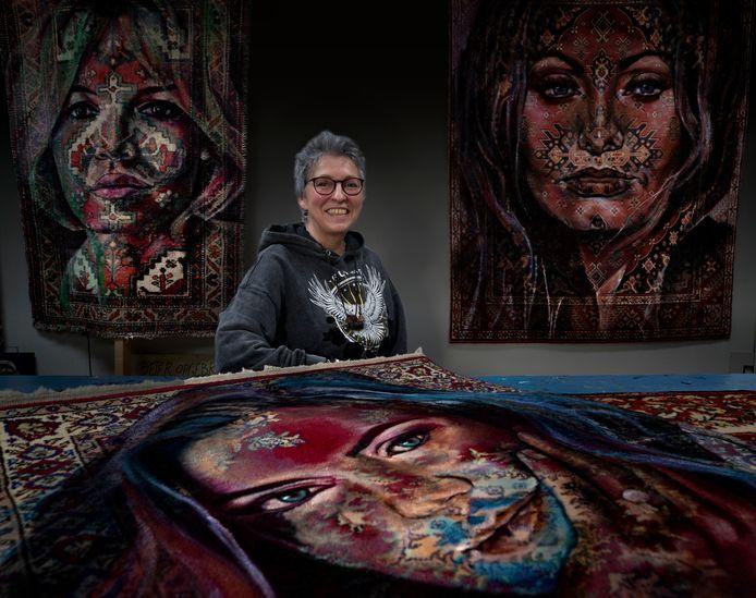 Kunstenares Anita Hoebergen uit Ommel bij haar beschilderde Perzische tapijten.