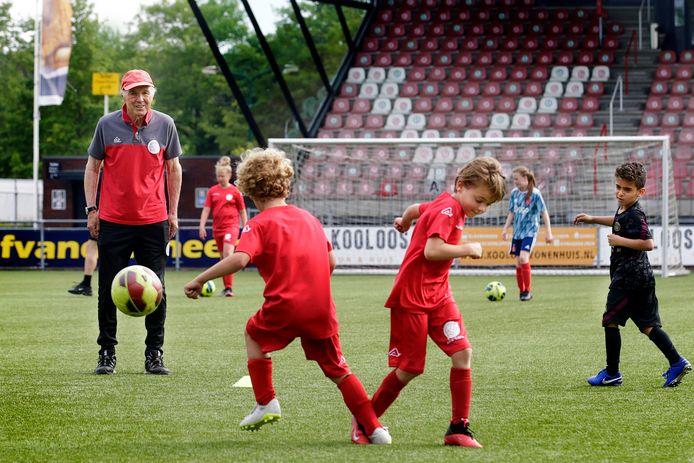 Joop Brand (links) kijkt op het complex van IJsselmeervogels naar de verrichtingen van jeugdspelers van 6 tot 13 jaar.