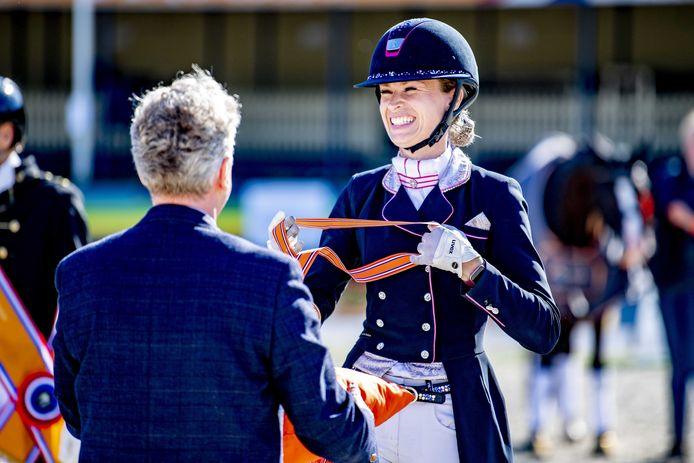 Dinja van Liere ontvangt haar medaille met een brede lach.