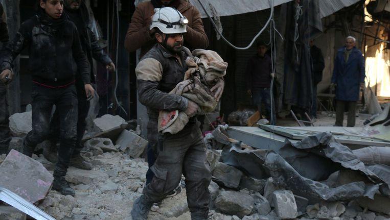 Een Syrische soldaat draagt een in een doek gewikkeld kind over het puin na een luchtaanval zaterdag in Aleppo. Beeld afp