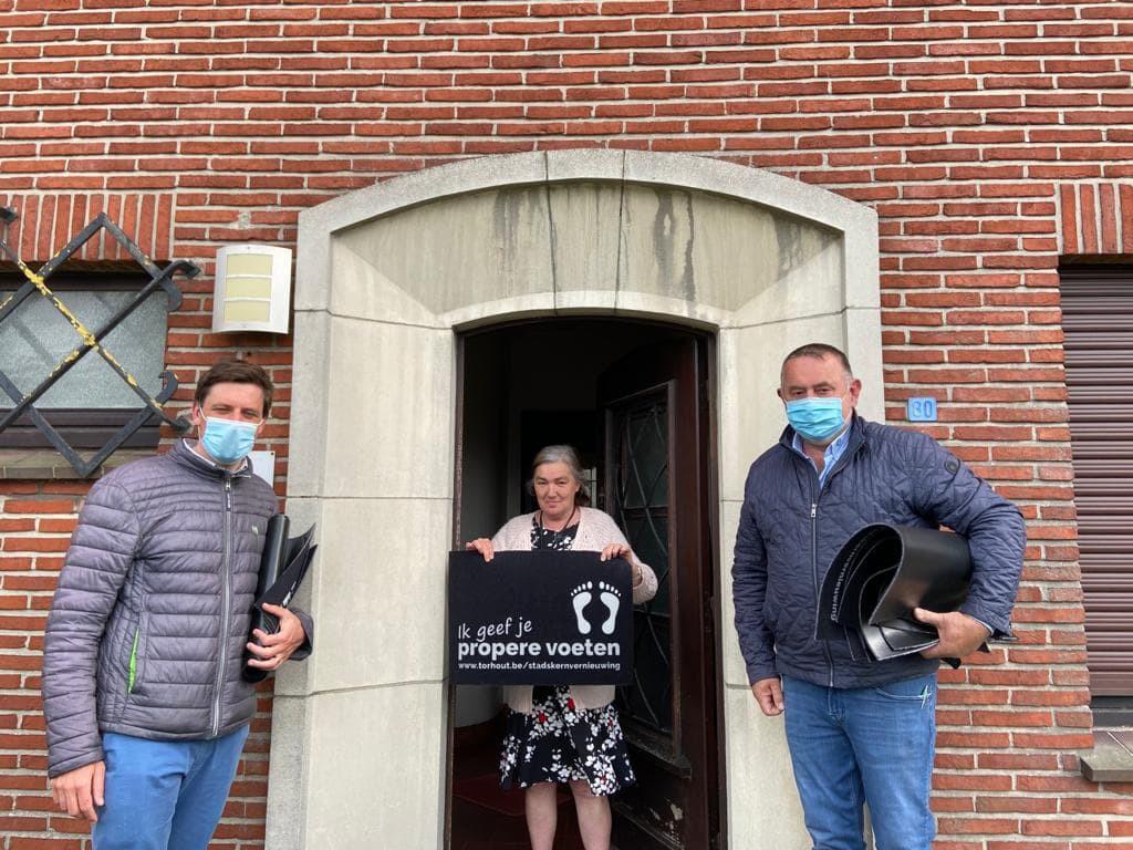 Burgemeester Kristof Audenaert en schepen van Openbare Werken Hans Blomme passeren met een deurmat bij een inwoonster.