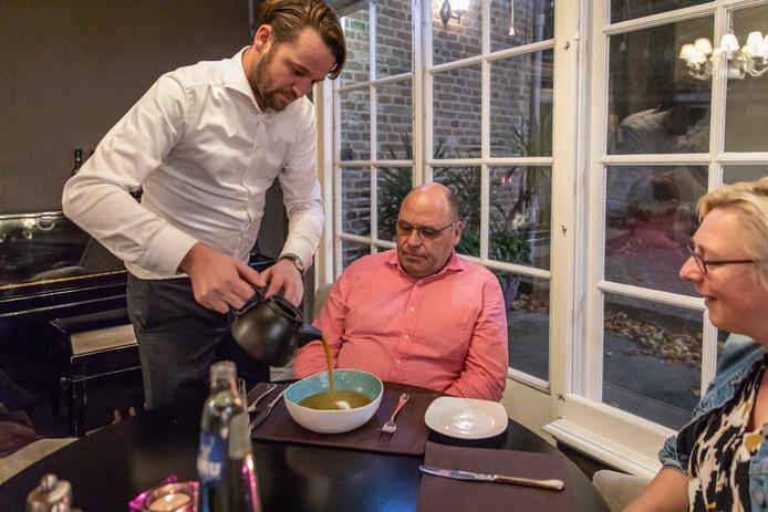 Gastheer Koen van der Plank schenkt de pompoensoep aan tafel in het bord.