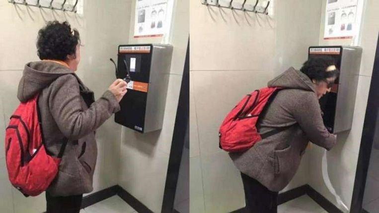 Een vrouw gebruikt een van de gezichtherkenners bij het openbare toiletgebouw in Peking.  Beeld Weibo