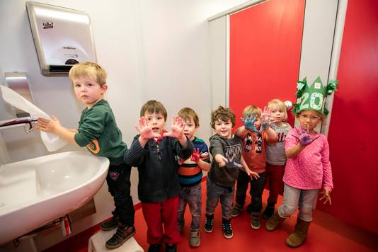 Kinderen staan keurig in de rij om hun handen te wassen.