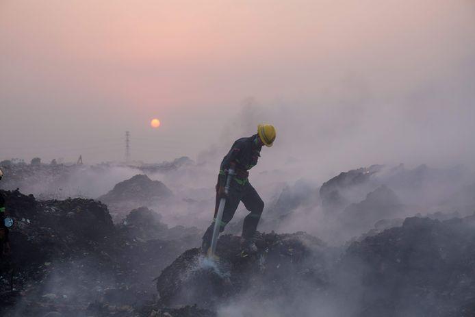Een brandweerman probeert een brand te blussen op een vuilnisbelt in de Birmese stad Yangon.