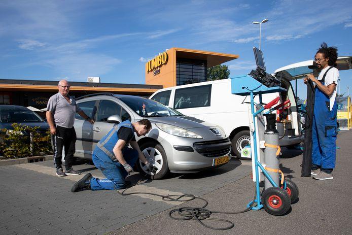Marijn Sieben controleert de bandenspanning van de auto van Chiel van Putten (l) in Nieuwerkerk. Rechts collega Serge Racamy.