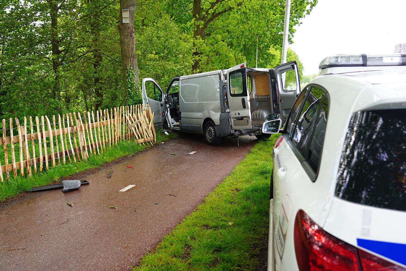 Busje botst tegen lantaarnpaal en hek in Tilburg.