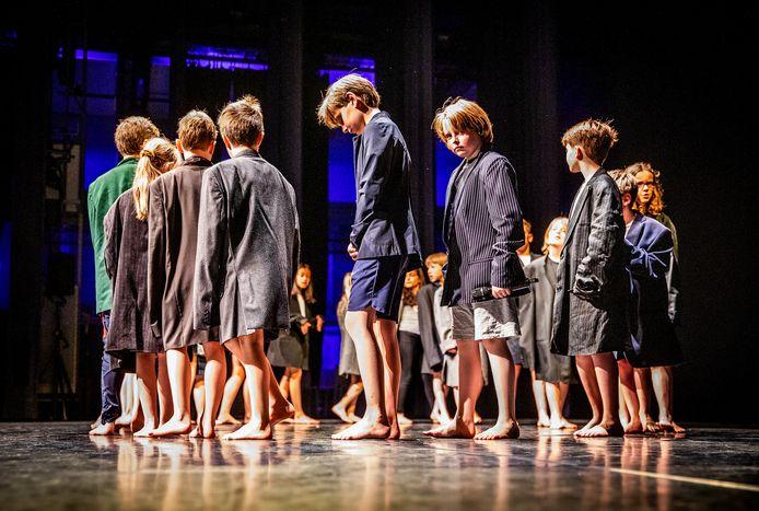 Leerlingen van groep acht van de Dr. H. Bavinckschool repeteren in de grote zaal van Schouwburg Kunstmin Dordrecht voor de voorstelling 'Reizen met eieren'. Een voor een geven ze de microfoon aan elkaar door.